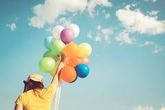 Χέρι κοριτσιών που κρατά τα πολύχρωμα μπαλόνια γίνοντα με μια αναδρομική επίδραση φίλτρων instagram, Στοκ Φωτογραφίες