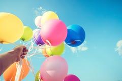 Χέρι κοριτσιών που κρατά τα πολύχρωμα μπαλόνια γίνοντα με μια αναδρομική επίδραση φίλτρων instagram, Στοκ Εικόνες