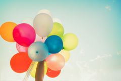 Χέρι κοριτσιών που κρατά τα πολύχρωμα μπαλόνια γίνοντα με μια αναδρομική επίδραση φίλτρων instagram Στοκ Εικόνες