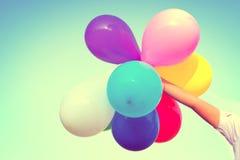 Χέρι κοριτσιών που κρατά τα πολυ χρωματισμένα μπαλόνια Στοκ φωτογραφία με δικαίωμα ελεύθερης χρήσης