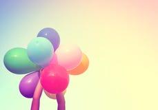 Χέρι κοριτσιών που κρατά τα πολυ χρωματισμένα μπαλόνια Στοκ Εικόνα