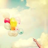 Χέρι κοριτσιών που κρατά τα πολύχρωμα μπαλόνια γίνοντα με έναν αναδρομικό τρύγο Στοκ Εικόνες
