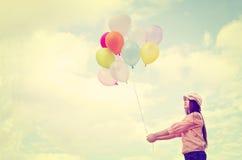 Χέρι κοριτσιών που κρατά τα πολύχρωμα μπαλόνια Στοκ εικόνες με δικαίωμα ελεύθερης χρήσης