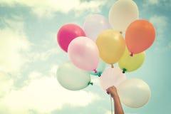Χέρι κοριτσιών που κρατά τα πολύχρωμα μπαλόνια Στοκ Εικόνα