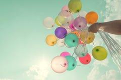 Χέρι κοριτσιών που κρατά τα πολύχρωμα μπαλόνια Στοκ Φωτογραφίες