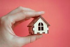 Χέρι κοριτσιών που κρατά το ξύλινο μικροσκοπικό σπίτι παιχνιδιών στο φως του ήλιου με το ρόδινο υπόβαθρο στοκ εικόνες