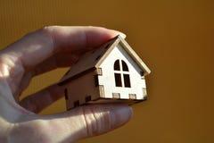 Χέρι κοριτσιών που κρατά το ξύλινο μικροσκοπικό σπίτι παιχνιδιών στο φως του ήλιου με το κίτρινο υπόβαθρο στοκ φωτογραφίες με δικαίωμα ελεύθερης χρήσης