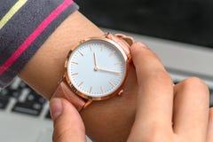 Χέρι κοριτσιών ` s με το wristwatch μπροστά από έναν φορητό προσωπικό υπολογιστή στοκ φωτογραφίες