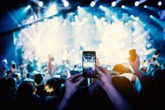 Χέρι - κρατημένη έξυπνη τηλεφωνική μαγνητοσκόπηση μια συναυλία στοκ εικόνα με δικαίωμα ελεύθερης χρήσης