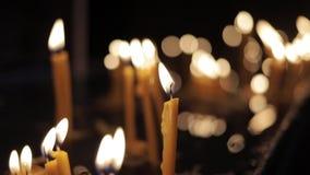 Χέρι - κρατημένος πυροβολισμός πολλών καίγοντας κεριών στο μαύρο υπόβαθρο στην εκκλησία απόθεμα βίντεο