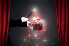 Χέρι μάγων με τη μαγική ράβδο που κάνει το δώρο Χριστουγέννων Στοκ Φωτογραφίες