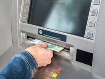 χέρι μετρητών καρτών του ATM που παρεμβάλλει την πλαστική γυναίκα απόσυρσης του s στοκ εικόνες
