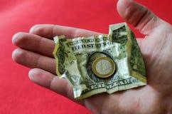 Χέρι με ένα ένα ευρο- νόμισμα σιδήρου και ένα αμερικανικό δολάριο έννοια οικονομική στοκ εικόνες