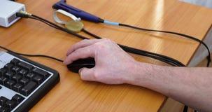 Χέρι με ένα ποντίκι υπολογιστών στον πίνακα απόθεμα βίντεο