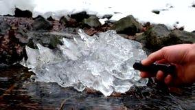 Χέρι με ισχυρό ελαφρύ λάμψης στο όμορφο μεγάλο κομμάτι του πάγου με τις αφηρημένες ρωγμές Πεσμένος καταρράκτης φυσητήρων παγακιών απόθεμα βίντεο