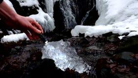 Χέρι με ισχυρό ελαφρύ λάμψης στο όμορφο μεγάλο κομμάτι του πάγου με τις αφηρημένες ρωγμές Πεσμένος καταρράκτης φυσητήρων παγακιών φιλμ μικρού μήκους