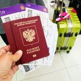 Χέρι με τα διαβατήρια και τα εισιτήρια αεροπλάνων ενάντια στο σκηνικό του SU στοκ φωτογραφία με δικαίωμα ελεύθερης χρήσης