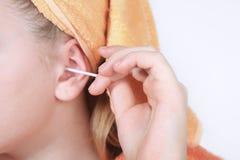 Χέρι με τα καθαρίζοντας αυτιά μιας βαμβακιού πατσαβουρών κινηματογραφήσεων σε πρώτο πλάνο υγιεινής Στοκ Φωτογραφία