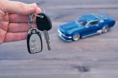 Χέρι με τα κλειδιά αυτοκινήτων και το μικρό πρότυπο αυτοκινήτων Στοκ Εικόνα