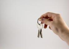 Χέρι με τα κλειδιά σε ένα άσπρο υπόβαθρο στοκ εικόνες
