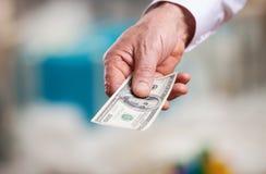 Χέρι με τα χρήματα σε ένα υπόβαθρο Χριστουγέννων Στοκ εικόνες με δικαίωμα ελεύθερης χρήσης