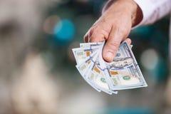 Χέρι με τα χρήματα σε ένα υπόβαθρο Χριστουγέννων Στοκ Φωτογραφίες