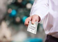 Χέρι με τα χρήματα σε ένα υπόβαθρο Χριστουγέννων Στοκ Φωτογραφία