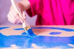 Χέρι με τα χρώματα βουρτσών με το μπλε χρώμα στοκ εικόνες