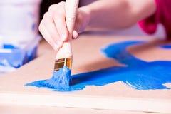 Χέρι με τα χρώματα βουρτσών με το μπλε χρώμα στοκ φωτογραφίες