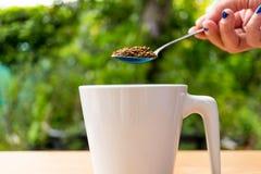 Χέρι με τεθειμένο τον κουτάλι καφέ σε ένα φλυτζάνι Στοκ εικόνες με δικαίωμα ελεύθερης χρήσης