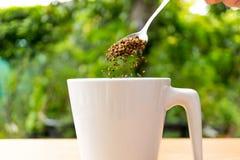 Χέρι με τεθειμένο τον κουτάλι καφέ σε ένα φλυτζάνι Στοκ Εικόνα