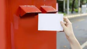 Χέρι με την κάρτα και πτώση στο κόκκινο ταχυδρομικό κουτί ταχυδρομείου Στοκ Εικόνες