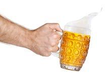 Χέρι με την κούπα του ραντίσματος της μπύρας στοκ εικόνες