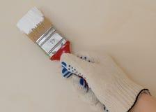 Χέρι με τη βούρτσα στο άσπρο χρώμα Στοκ φωτογραφία με δικαίωμα ελεύθερης χρήσης