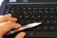 Χέρι με τη μάνδρα στο μαύρο lap-top πληκτρολογίων Στοκ φωτογραφία με δικαίωμα ελεύθερης χρήσης