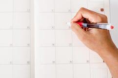 Χέρι με τη μάνδρα στην ημερολογιακή σελίδα Στοκ Εικόνες