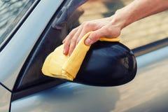 Χέρι με τη στιλβωτική ουσία κουρελιών ο δευτερεύων καθρέφτης του αυτοκινήτου Στοκ φωτογραφία με δικαίωμα ελεύθερης χρήσης