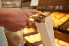 Χέρι με τις λαβίδες που παίρνουν το κουλούρι στο αρτοποιείο ή το παντοπωλείο στοκ εικόνες