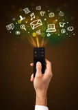 Χέρι με τον τηλεχειρισμό και τα κοινωνικά εικονίδια μέσων Στοκ Φωτογραφίες