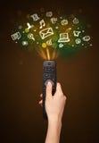 Χέρι με τον τηλεχειρισμό και τα κοινωνικά εικονίδια μέσων Στοκ Εικόνα