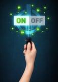 Χέρι με τον τηλεχειρισμό και τα on-off σήματα Στοκ εικόνες με δικαίωμα ελεύθερης χρήσης