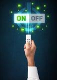 Χέρι με τον τηλεχειρισμό και τα on-off σήματα Στοκ Φωτογραφία