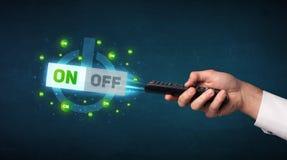 Χέρι με τον τηλεχειρισμό και τα on-off σήματα Στοκ φωτογραφία με δικαίωμα ελεύθερης χρήσης