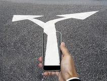 Χέρι με το έξυπνο τηλέφωνο και τις διπλής κατεύθυνσης κατευθύνσεις βελών από το τηλέφωνο στο δρόμο, επιχειρησιακή έννοια στοκ εικόνα