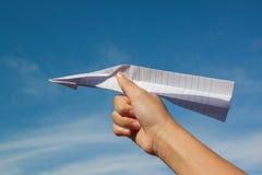 Χέρι με το αεροπλάνο εγγράφου ενάντια στο μπλε ουρανό Στοκ Εικόνα