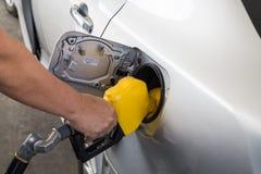 Χέρι με το ακροφύσιο που τροφοδοτεί με καύσιμα την αμόλυβδη βενζίνη στο αυτοκίνητο στοκ φωτογραφίες