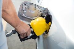Χέρι με το ακροφύσιο που τροφοδοτεί με καύσιμα την αμόλυβδη βενζίνη στο αυτοκίνητο στοκ φωτογραφία