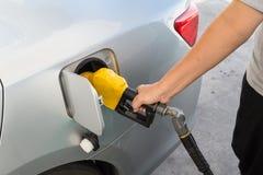Χέρι με το ακροφύσιο που τροφοδοτεί με καύσιμα την αμόλυβδη βενζίνη στο αυτοκίνητο στοκ φωτογραφία με δικαίωμα ελεύθερης χρήσης