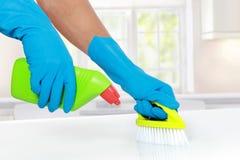 Χέρι με το γάντι που χρησιμοποιεί την καθαρίζοντας βούρτσα που καθαρίζει επάνω Στοκ Εικόνα