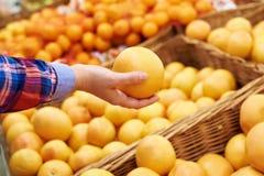 Χέρι με το γκρέιπφρουτ στην υπεραγορά φρούτων στοκ εικόνες